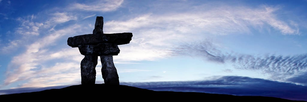 inuksuk in the foreground on a hill in the shadows with the sky and clouds in the background