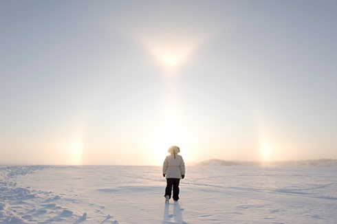 We see a person walking away from the camera dressed in a white winter jacket and black winter pants. They're walking in an open area by themselves on a sunny winter day.